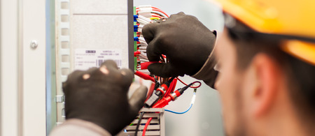 Foto de Closeup of electrician engineer works with electric cable wires of fuse switch box. Electrical equipment - Imagen libre de derechos