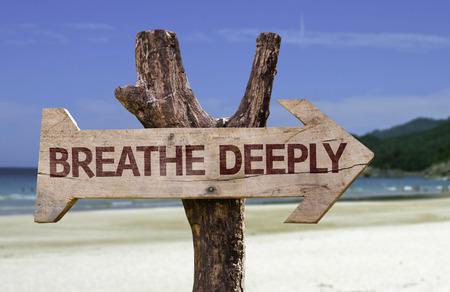 Photo pour Breathe deeply sign with arrow on beach background - image libre de droit