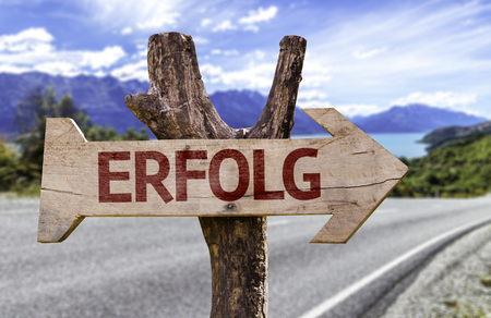 Erfolg (success in German) sign with arrow on road background
