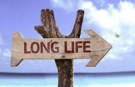 Foto de Long life sign with arrow on beach background - Imagen libre de derechos