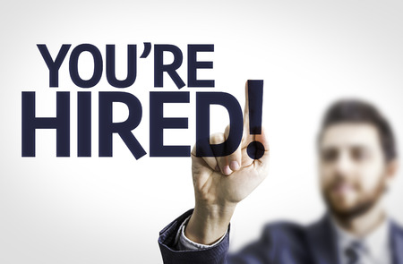 Photo for Business man pointing to transparent board with text: You're hired! - Royalty Free Image