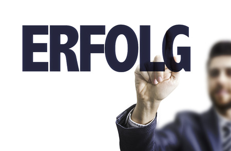 Business man pointing to transparent board with text: Erfolg (success in German)