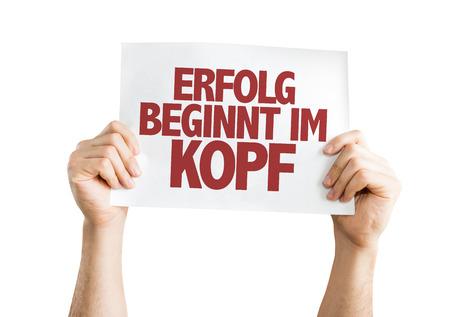 Hands holding cardboard on white background with text: Erfolg beginnt im kopf (success begins in the mind in German)