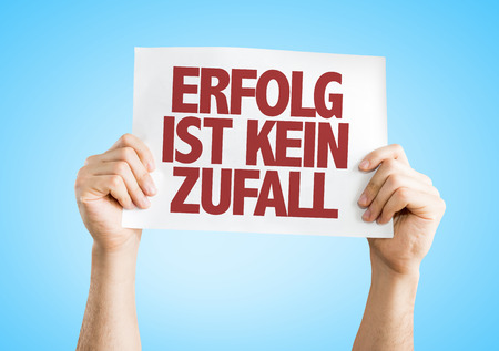 Hands holding cardboard on blue background with text: Erfolg ist kein zufall (success is no accident in German)