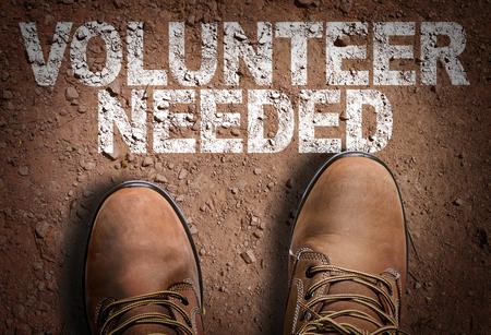 Foto de Text on road with boots background: Volunteer needed - Imagen libre de derechos