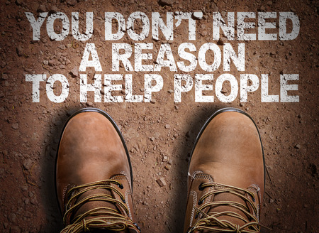 Foto de Text on road with boots background: You don't need a reason to help people - Imagen libre de derechos