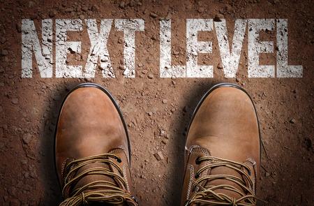 Photo pour Text on road with boots background: Next level - image libre de droit