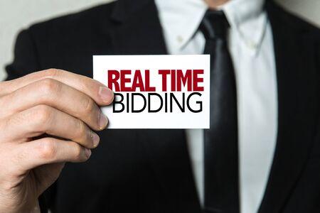 Foto de Man holding real time bidding card - Imagen libre de derechos