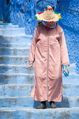Photo pour An old woman strolls through the streets of Chefchaouen, the blue town in Morocco, with her traditional costume - image libre de droit