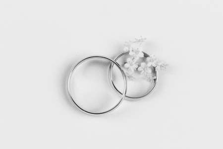 Photo pour a pair of gold wedding rings and small white flowers in a ring on a white background, top view flat lay, black and white photo - image libre de droit