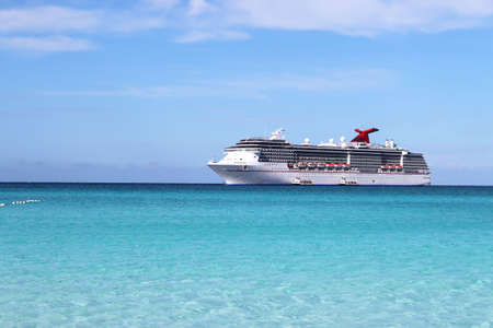 Cruise ship in the clear blue Caribbean ocean with boat tenders picking up passengers going to shore