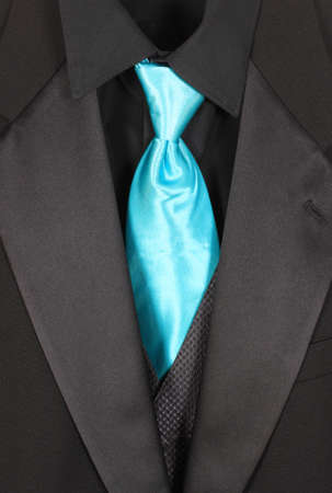 Black dressy formal three piece suit with shirt, vest and blue tie