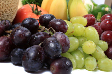 Three different types of grapes in red, green and black along with other healthy vegetables and fruits like bananas and tomatoes