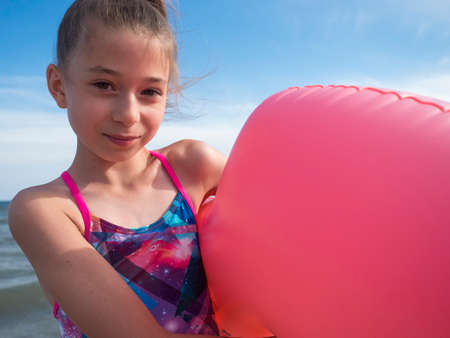 Photo pour A teenage girl on the beach by the sea with an inflatable big pink circle. Selective focus - image libre de droit