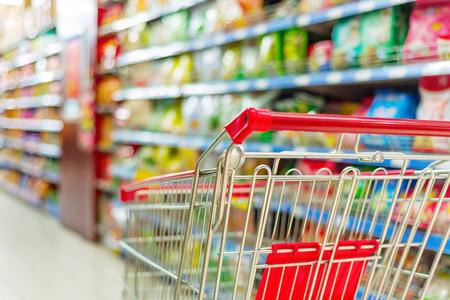 Foto de Supermarket interior, empty red shopping cart. - Imagen libre de derechos