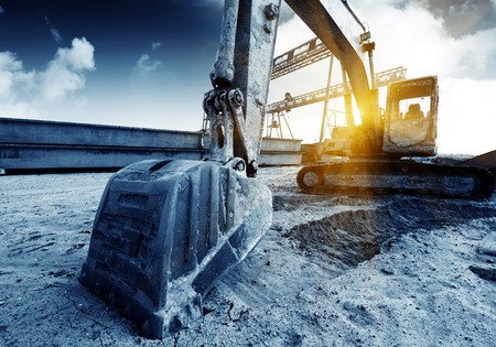 Foto per Big excavator on new construction site, in the background the blue sky and sun - Immagine Royalty Free