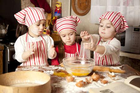 Three little chefs enjoying in the kitchen making big mess  Little girls making bread in the kitchen