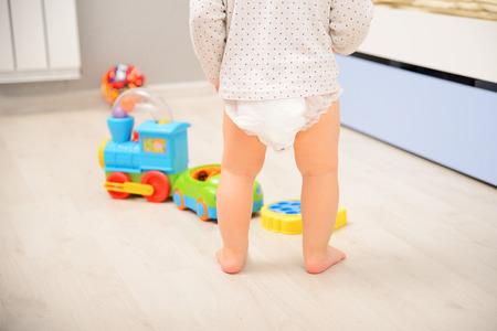 Photo pour Baby walking on wooden floor in diaper pants. Back view - image libre de droit
