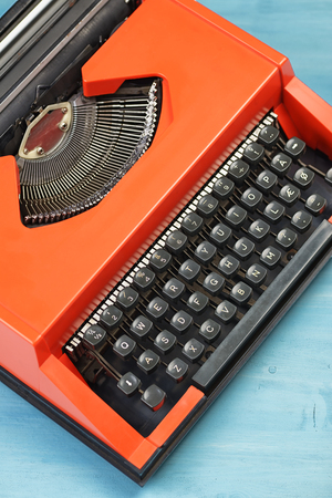 Photo pour Red typewriter on the blue desk or table. Top view - image libre de droit