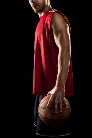 Athletic basketball player holding ball isolated on black background