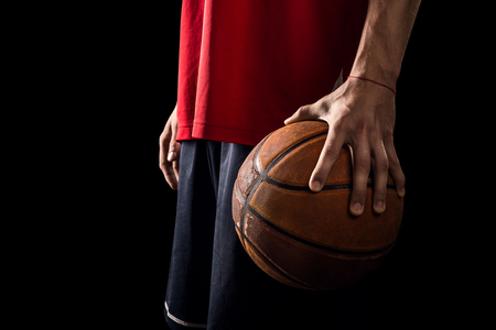 Photo pour Player Holds a Basketball ball in hand on the black background - image libre de droit