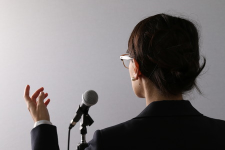 Photo pour View from behind of a businesswoman standing in front of a microphone gesturing as she gives a presentation or speech - image libre de droit