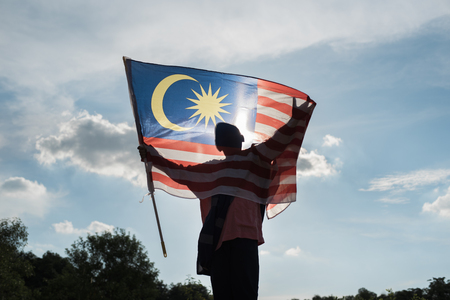 Foto de Silhouette of a boy holding the malaysian flag celebrating the Malaysia independence day - Imagen libre de derechos