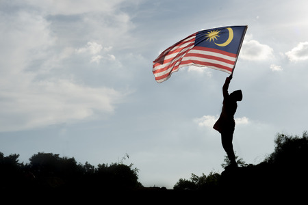 Photo pour Silhouette of a boy holding the malaysian flag celebrating the Malaysia independence day - image libre de droit