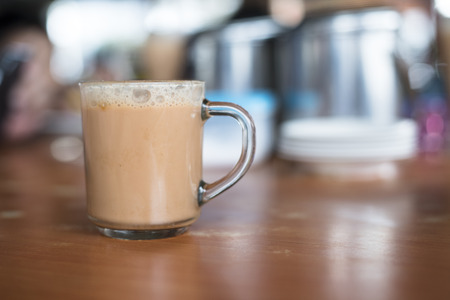 Photo pour a glass of tea with milk on a table at mamak restaurant.famous or popular drink in malaysia.Malaysian favorite drink known as Teh Tarik.signature menu at mamak stall,cafe,restaurant or bistro - image libre de droit
