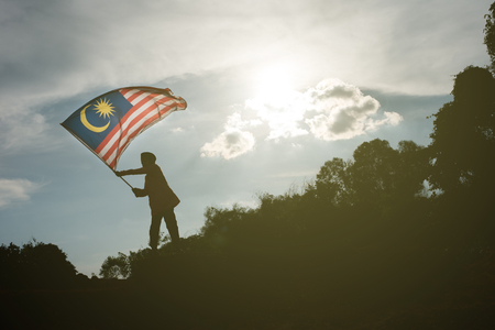 Photo pour Silhouette of a young asian boy holding the malaysian flag celebrating the Malaysia independence day and Malaysia day - image libre de droit
