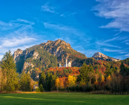Foto de Amazing view on Neuschwanstein Castle with picturesque sky and colorful trees at autumn sunny day, Bavaria, Germany - Imagen libre de derechos