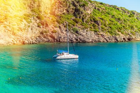 Foto de View of the sea bay and a sailing catamaran near a steep coast of the island of Crete, Greece - Imagen libre de derechos