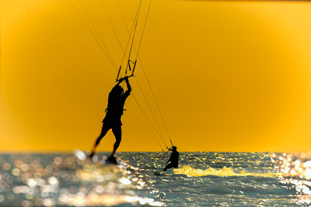 Photo for Silhouette of kitesurfer, jumping over the sea on sunset sky background. Photo toned - Royalty Free Image