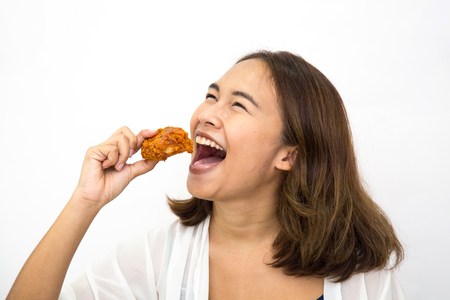 Photo pour Happy young asian woman with fried chicken, she holding fried chicken in her hand, isolated white background - image libre de droit