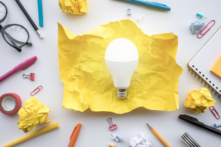 Photo pour Inspiration creativity concepts with lightbulb in paper crumpled ball on worktable.Business ideas solution and human performance.Top view - image libre de droit