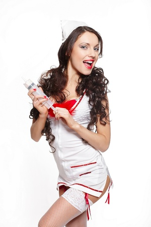 Sexy beautiful smiling female brunette doctor with big syringe red lingerie white stocking and red lips on a white background long curly hair