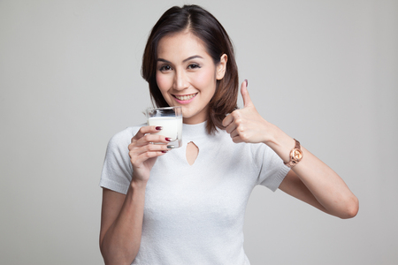 Photo pour Healthy Asian woman drinking a glass of milk thumbs up on gray background - image libre de droit