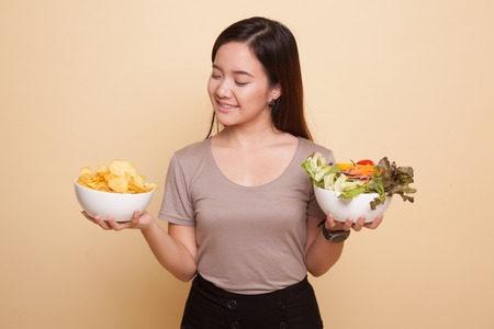 Foto für Young Asian woman with potato chips and salad on beige background - Lizenzfreies Bild
