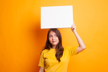 Foto de Young Asian woman with white blank sign in yellow dress on yellow background - Imagen libre de derechos
