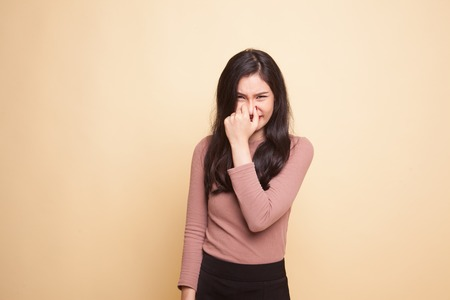Photo for Young Asian woman  holding her nose because of a bad smell on beige background - Royalty Free Image