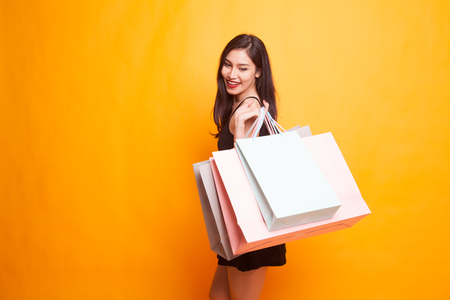 Photo for Young Asian woman happy with shopping bag on yellow background - Royalty Free Image