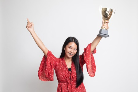 Successful number one winner young asian woman holding a trophy on white background