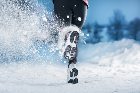 Athlete woman is running during winter training outside in cold snow weather