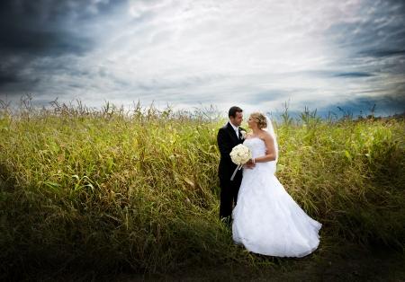 Foto de Bride and groom are posing outdoors - Imagen libre de derechos