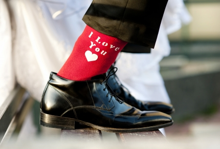 Photo pour Groom s funny feet with love sign on red socks  - image libre de droit