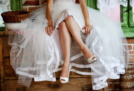 Foto de Detail of bridal legs with shoes sitting on the wooden table - Imagen libre de derechos