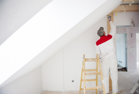 Photo for Construction worker is painting the wall in new house - Royalty Free Image