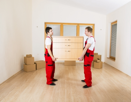 Photo for Movers in new house with lot of boxes behind them  - Royalty Free Image