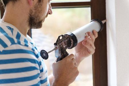 Photo pour Man applying silicone sealant with caulking gun - image libre de droit