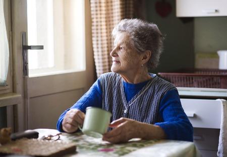 Foto de Old woman is drinking tea in her country style kitchen - Imagen libre de derechos